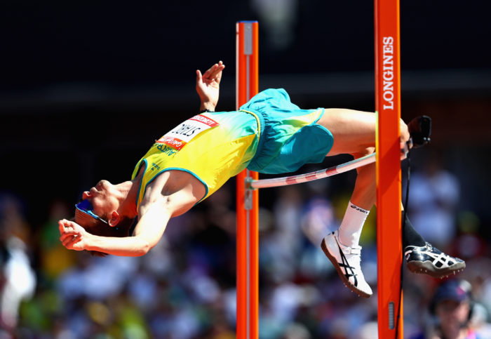 A high jumper clears the bar.